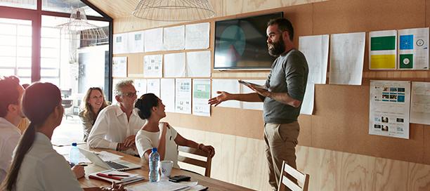 Hombre dirigiendo un taller presencial con un equipo de personas