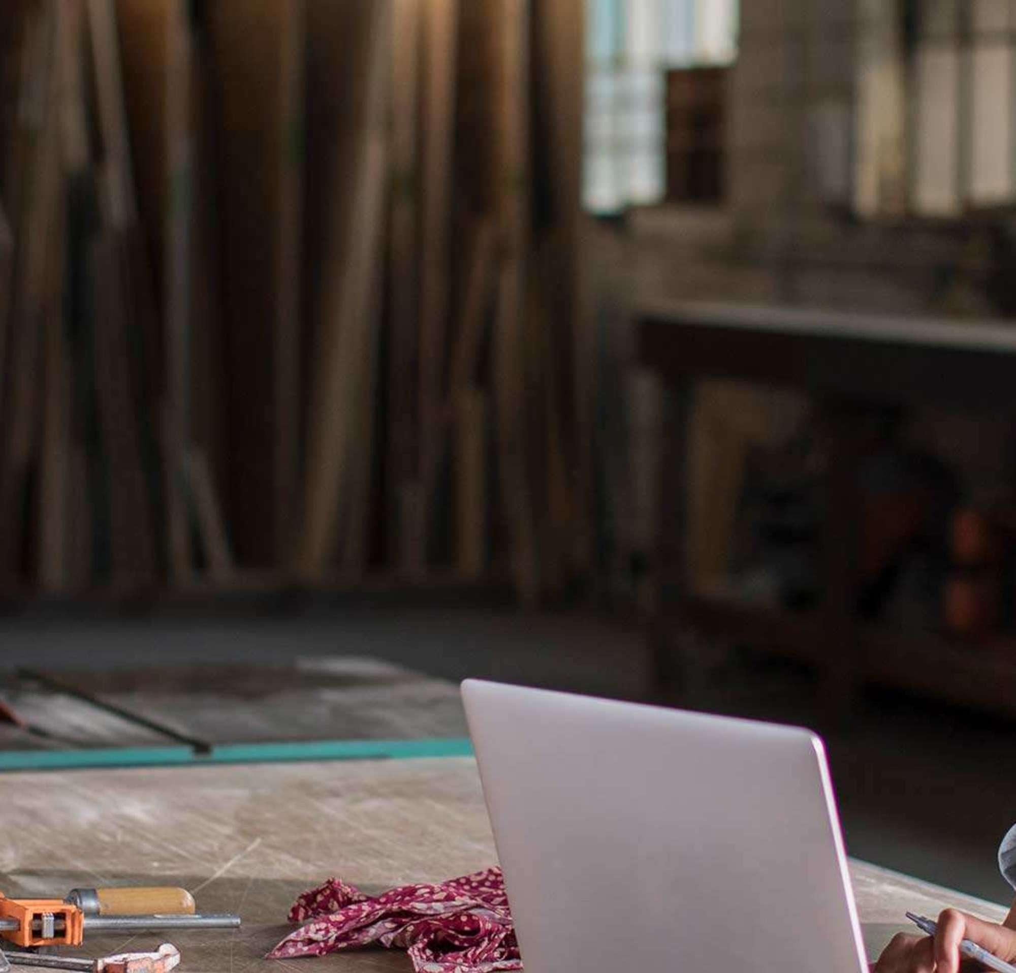 Mujer joven trabajando desde un portátil en su carpintería