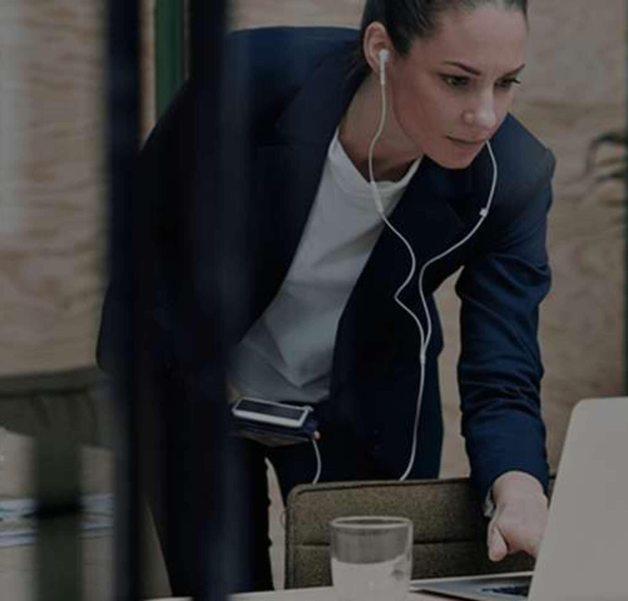 Mujer con auriculares trabajando en una laptop y con su teléfono en las manos.