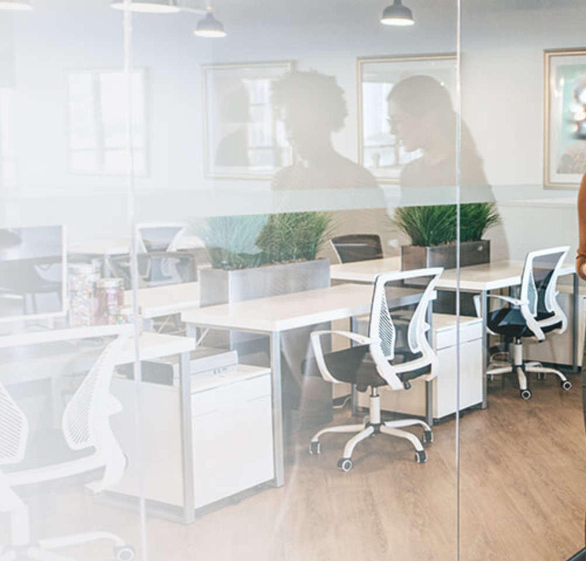 Dos mujeres en una sala de reuniones de la oficina caminando y hablando mientras miran un documento.