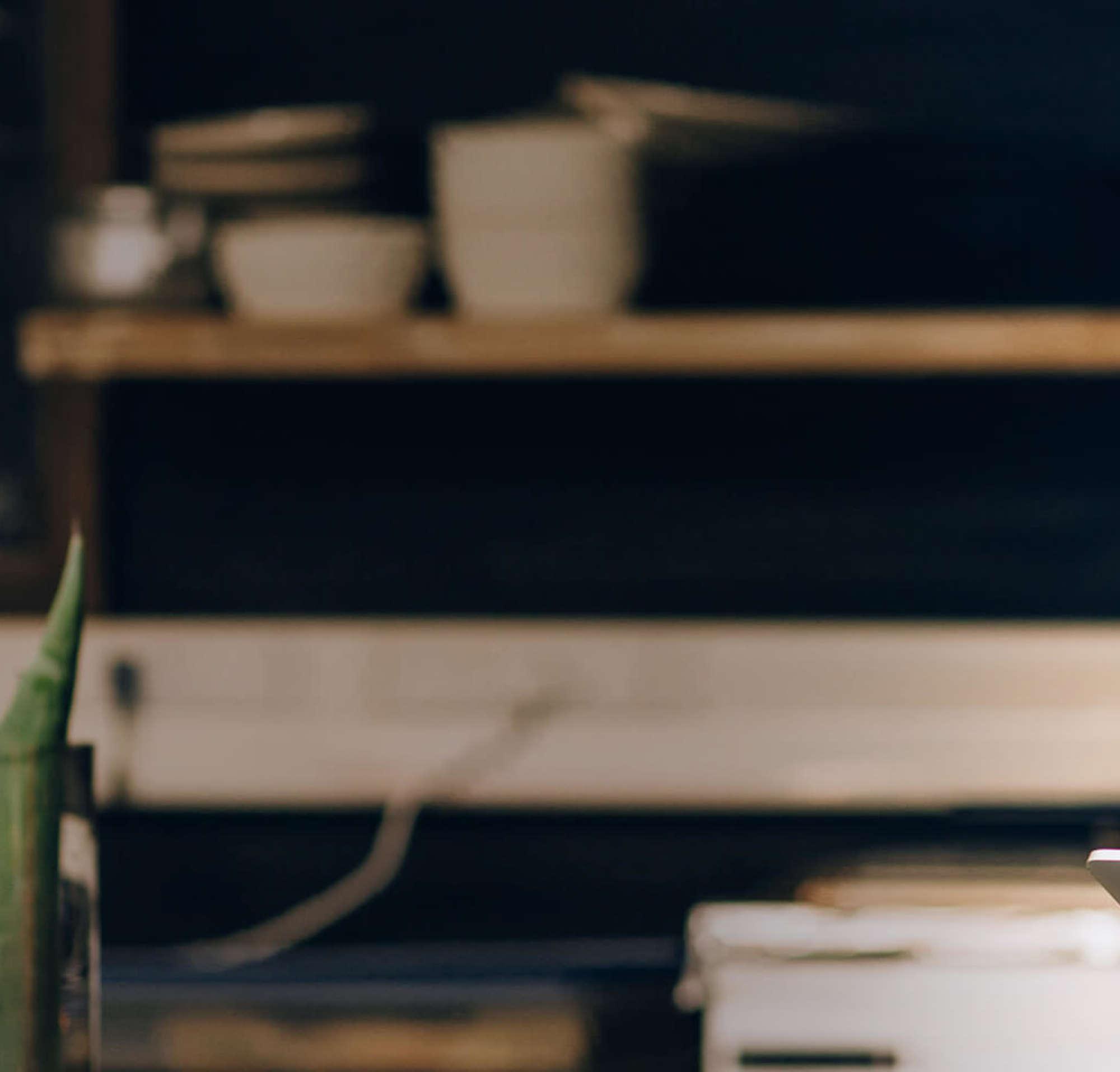 Una mujer en la cocina de un restaurante, mirando una tableta