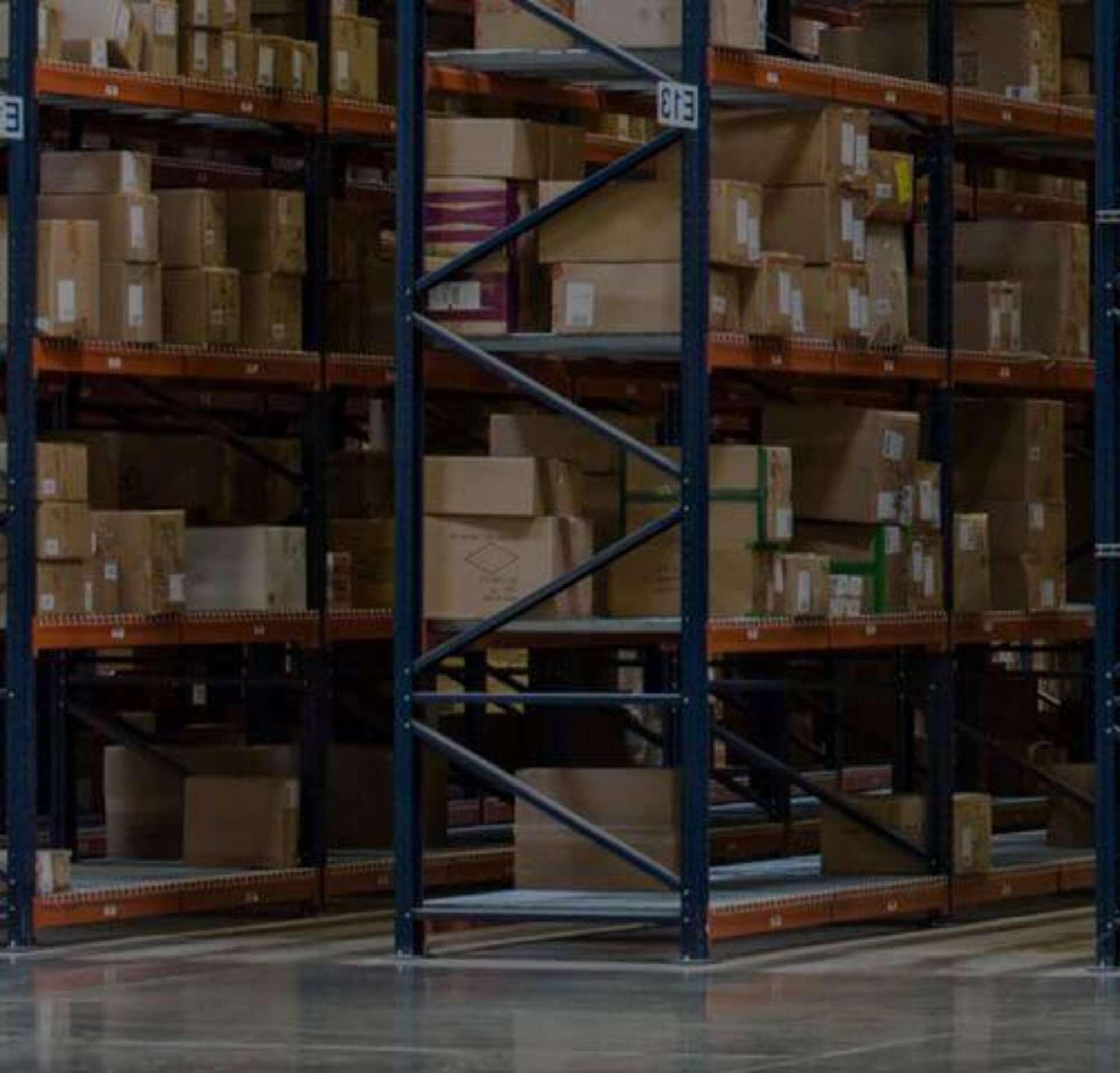 Dos personas en un almacén lleno de cajas.