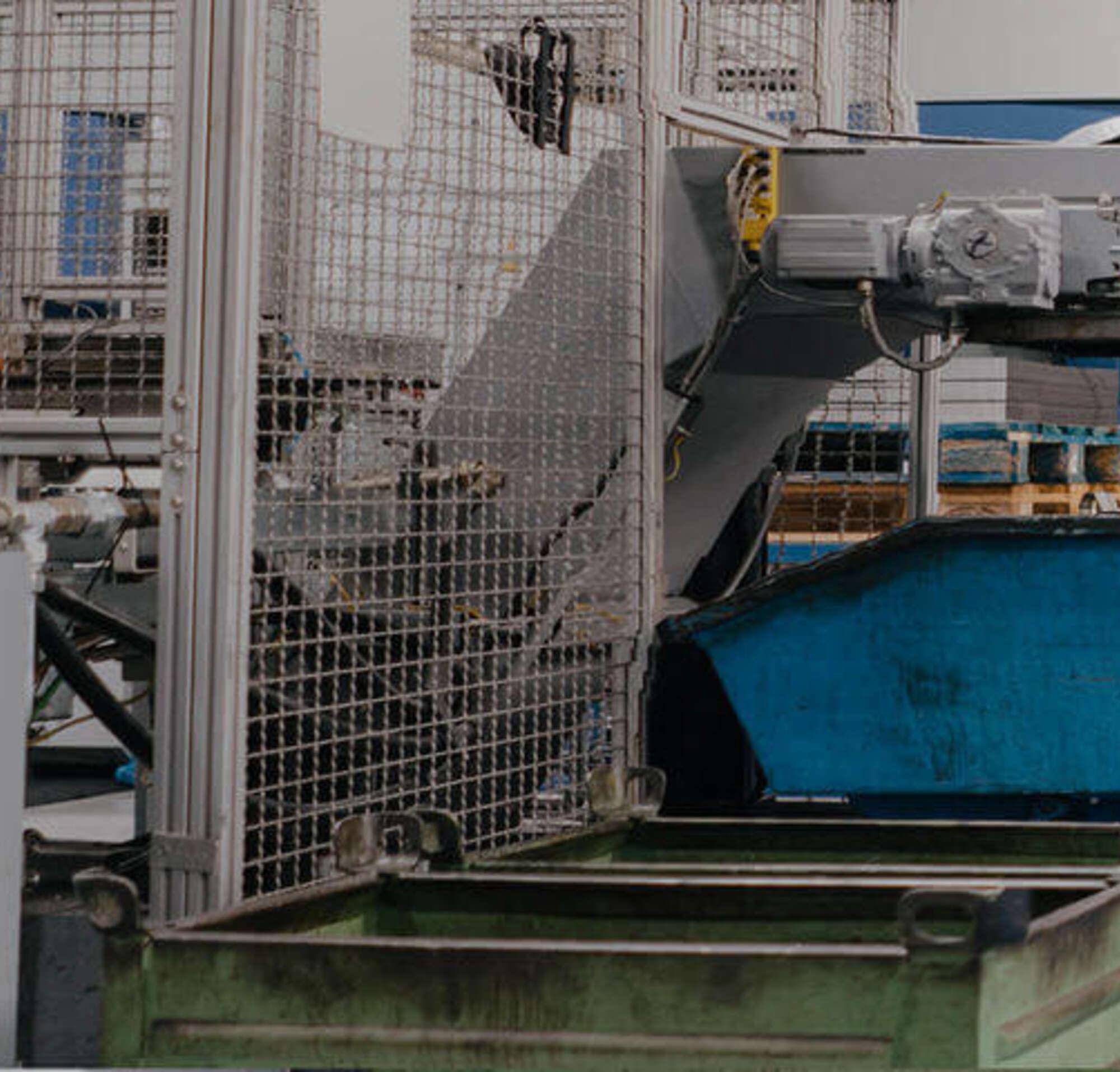 Un hombre en un traje caminando con una obrera dentro de una fábrica con maquinaria grande.