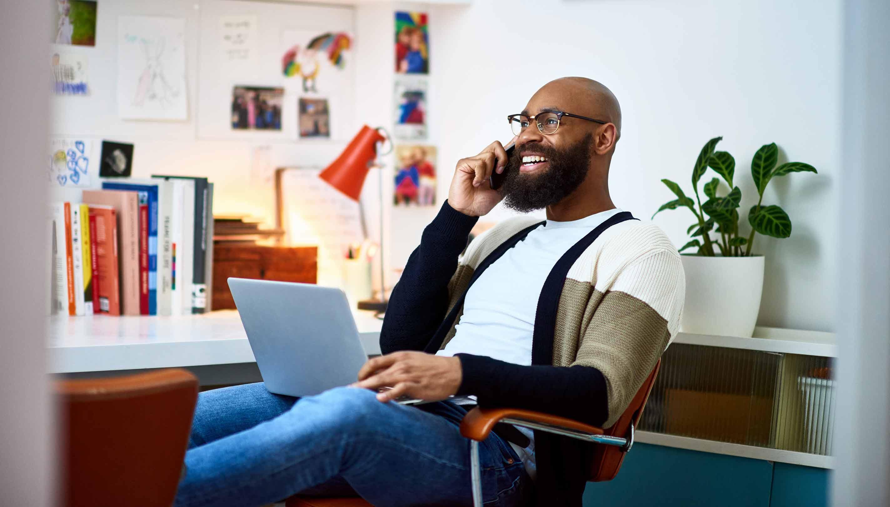 Hombre sonriendo mientras trabaja desde una moderna oficina en casa